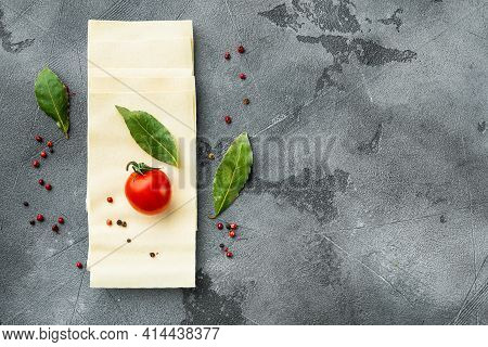 Dried Uncooked Lasagna Pasta Sheets Set, With Seasoning And Herb, On Gray Stone Background, Top View
