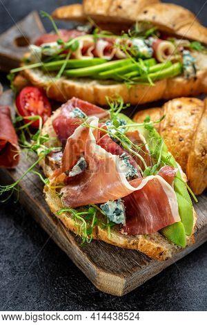 Close Up Croissant Sandwich With Jamon Serrano, Prosciutto Ham , Blue Cheese, Avocado, Microgin. Med