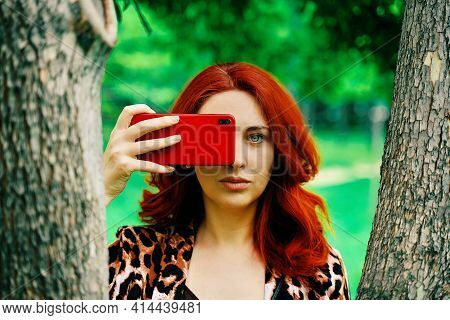 Girl In The Park. Red-haired Woman Takes A Picture On Her Phone Between The Trees. Summer Walk In Th