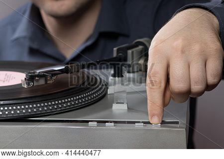 A Man Presses A Gramophone Vinyl Record Player Button. Vintage Record Player Spins.
