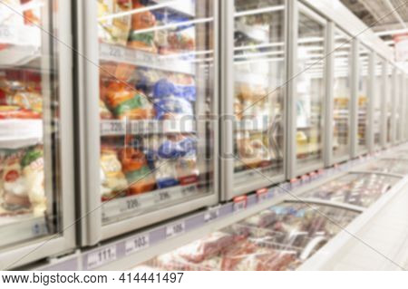 Glass Display Cases In The Frozen Food Section Of A Supermarket. Blurred.