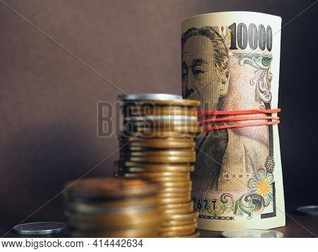 Japanese Money: Ten Thousand Yen Bills And Stacks Of Coins Close-up. Focus On The Number 10000. Bank