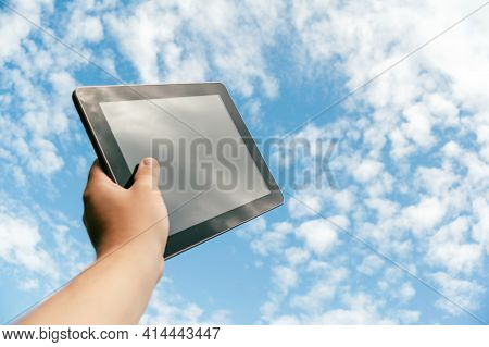 A Man Is Holding A Black Tablet, Against The Background Of The Sky.