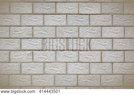 The Wall Of The Building Is Made Of Gray Concrete Blocks. Background With Vignetting. The Seams Form