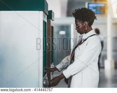 Side View Of An African Female Withdrawing The Money From A Bank Card Using A Street Atm Machine; Bl