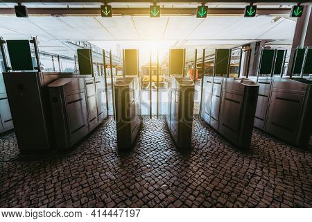 The Row Of Turnstiles On The Paving-stone With Closed Glass Doors And Green Arrows Above Allowing Pa