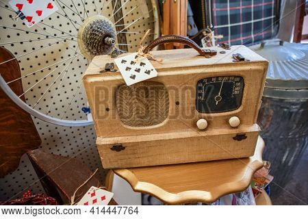 Antique vintage radio in a display of old collectibles for sale SHALLOW FOCUS, ZOOM IT ITS ON THE LEFT FRONT SPEAKER OF THE RADIO, AND THE KNOBS ON THE RIGHT, THE TOPISNOT THE FOCUS, THE FRONT IS