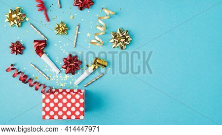 Top View Photo Of Birthday Composition Blast Of Tinsel Sparkles Serpentine Red Yellow Golden Ribbon