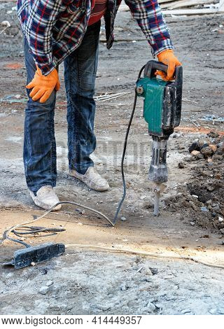 A Construction Worker In A Plaid Work Shirt And Blue Jeans Loosens Dense Soil With An Electric Jackh