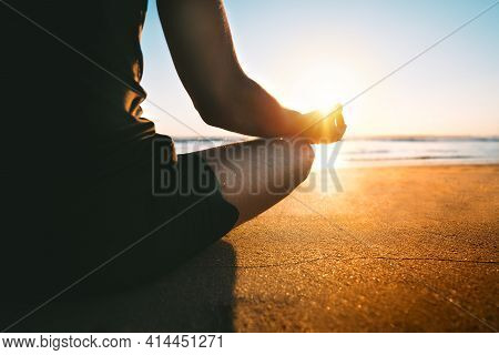 Man Meditates On The Beach At Sunset Or Sunrise. Sitting On The Sand In Easy Pose Or Sukhasana With