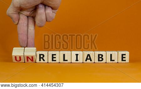 Unreliable Or Reliable Symbol. Businessman Turns Wooden Cubes And Changes The Word Unreliable To Rel