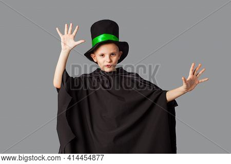 Young Magician Performing A Trick. Little Boy Wearing Top-hat And Black Magician Cloak.