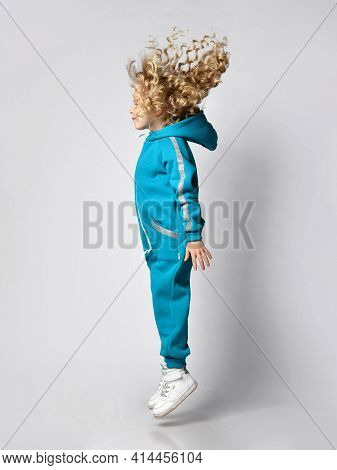Side View Of A Girl In Warm Sportswear, Fashionable Sportswear, Jumping Up At The Studio. Child Beau