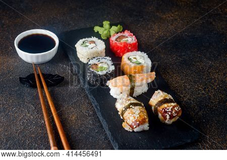 Tasty Sushi Rolls Set On Black Plate With Sauces, Chopsticks, Ginger And Wasabi On Dark Table. Sushi
