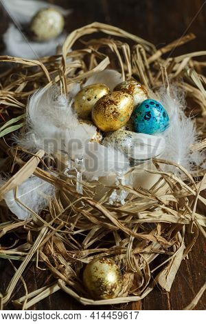 Gilded And Painted Easter Eggs In A Nest Of Twigs And Feathers. Close-up, Selective Focus. Rustic St