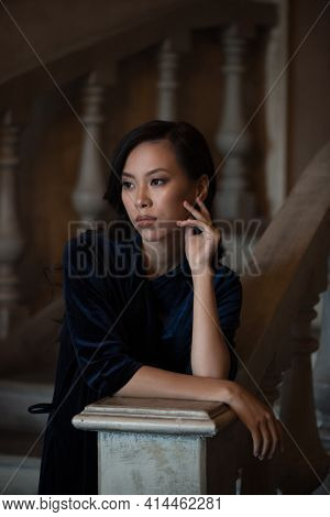 Young woman leans on the stone railing