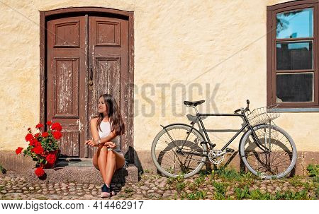 Quizzical Girl Sits Outside Her Faded Wooden Door Next To Her Bicycle In This Retro Hipster Image