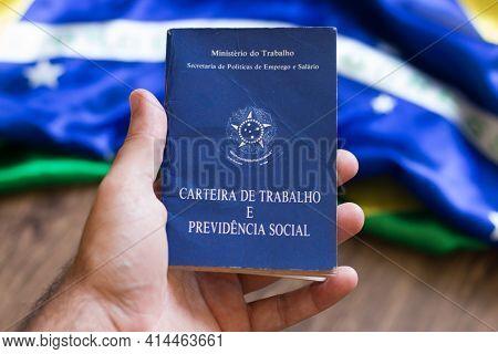 Hand Holding Brazilian Work Portfolio With Brazilian Flag In The Background.