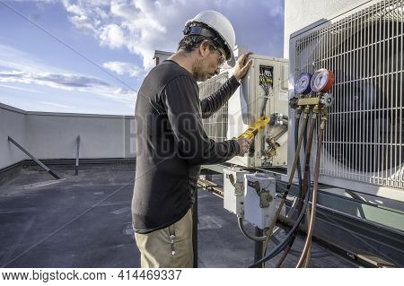 Professional Hvac Technician Taking An Amperage Reading On A Mini-split Ductless Air Conditioning Sy