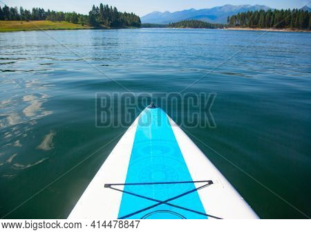 Title A paddle board floating on a beautiful mountain lake in Montana. Point of view photo of a scenic natural background