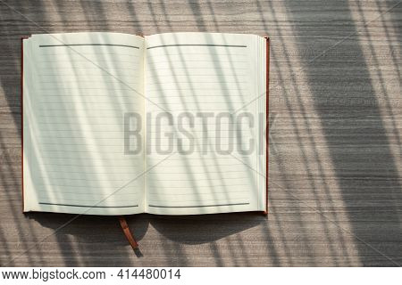 Top View Of Open Notebook On Wood Table With Blank Pages, Natural Light And Shadow Reflection Across