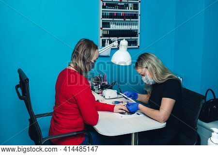 Closeup Of Milling Nails In A Beauty Salon. A Woman Gets A Manicure For Her Nails. Beautician Polish