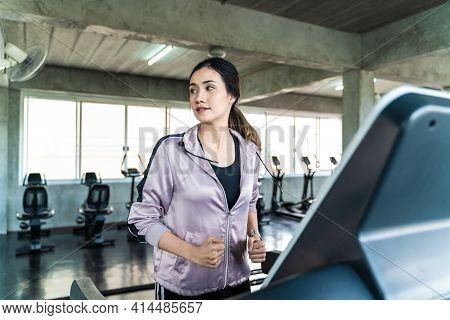 Smiling Asian Women Running On Treadmill In Fitness Sport Gym