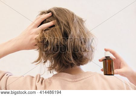 Back View Of A Woman With Hair Oil Bottle. Woman Touchinh Her Head And Holding Argan Or Coconut Or A