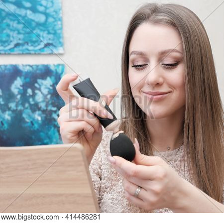Young Woman Applying Make Up Foundation On A Sponge At Home. Self Make-up, Real Peolpe. Woman Gets R