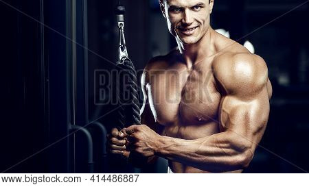 Fit Man Training Arm Muscles At Gym.
