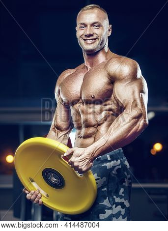 Fit Man Training Training Abs Muscles At Gym. Pumping Up Abdominal Exercise. Close Up Muscles At Wor