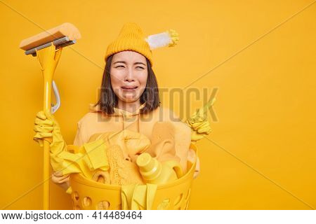 Upset Asian Woman Janitor Feels Sad And Tired Uses Mop For Cleaning House Poses Near Basin With Laun