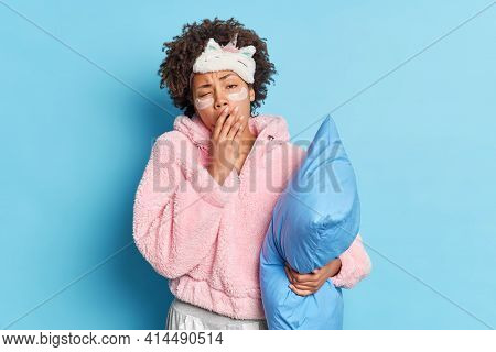 Exhausted Sleepless Woman Has Curly Hair Yawns Covers Mouth Dressed In Nightwear Holds Pillow Wants