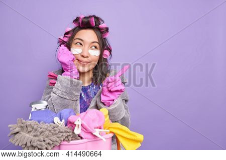 Photo Of Dreamy Satisfied Asian Woman Busy Doing Laundry At Home Points Aside On Blank Copy Space Ag
