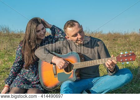 Happy Young People. The Guy Plays Guitar. The Girl Listens To Music