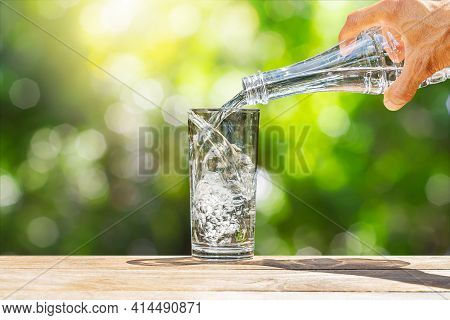 Hand Holding Drinking Water Bottle Pouring Into Glass On Wooden Table On Blurred Green Nature Backgr