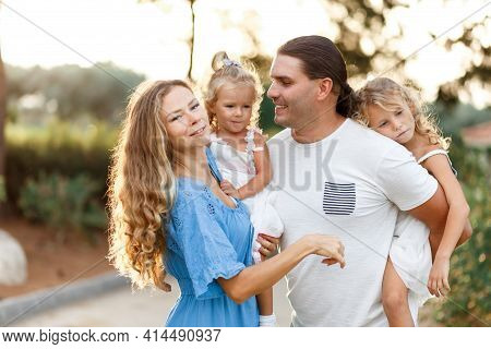 Young Happy Family Of Three Having Fun Together Outdoor. Pretty Little Daughters On Father Back. Par