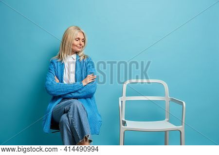 Photo Of Satisfied Middle Aged Woman Keeps Arms Crossed Looks At Empty Chair Wears Casual Jumper And