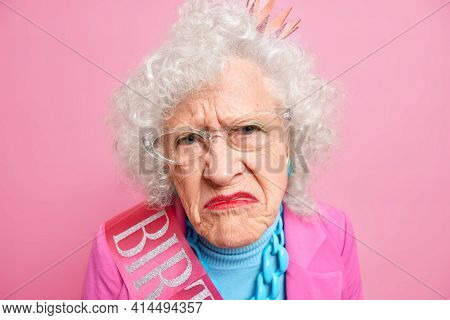 Close Up Shot Of Displeased Wrinkled Grandmother Smirks Face Looks Unhappily At Camera Has Bright Ma