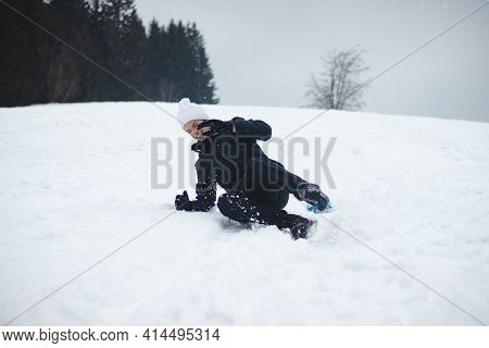 Young Boy With A White Cap Laughs At His Own Stupidity. The Teenager Was Riding On A Ski Slope On A