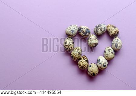 Quail Eggs In The Shape Of A Heart. Quail Eggs On Violet Background