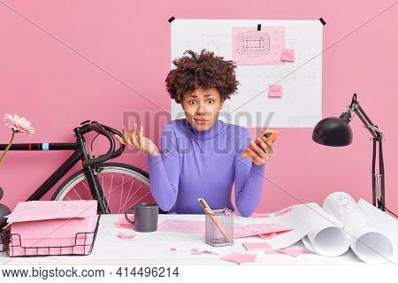 Puzzled Dark Skinned Woman Works At Desktop Holds Mobile Phone Checks Newsfeed Expreses Doubt Has Sk