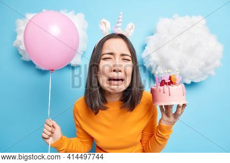 Depressed Crying Asian Woman Feels Lonely And Dejected On Her Birthday Holds Festive Cake And Inflat