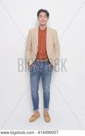 full length handsome casual man wearing suit with brown shirt with blue jeans , brown shoes  hands in pocket posing in studio