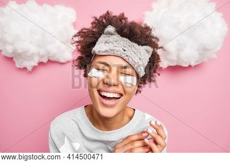 Headshot Of Positive Dark Skinned Woman With Curly Hair Closes Eyes Smiles Broadly Shows Teeth Dress