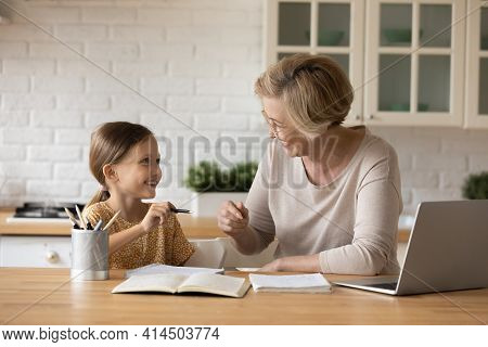 Smiling Grandmother Help Granddaughter With Homework Assignment