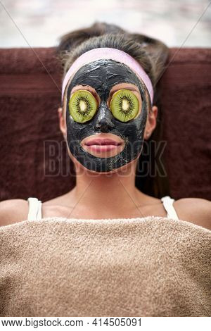 Woman with nutritious black mask on face and slice of kiwi on eyes