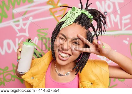 Cheerful Teen Girl With Dreadlocks Golden Teeth Makes Peace Or Victory Gesture Makes Graffiti With A