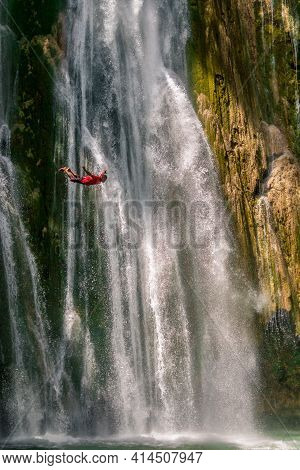 El Limon, Dominican Republic - April 2, 2016: Man Jumping Of Waterfall In Deep Rain Forest Jungle