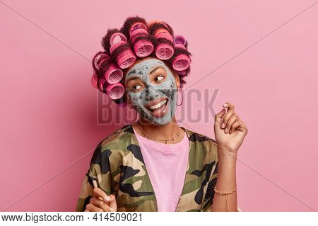 Isolated Shot Of Positive Woman Looks Aside Smiles Broadly Raises Arm Applies Hair Rollers Beauty Ma